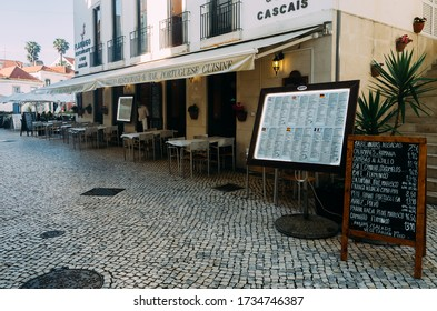 Cascais, Portugal - May 18, 2020: Waiter wearing face mask outside an empty restaurant patio during the descalation of lockdown phase during the Coronavirus Covid-19 oubreak