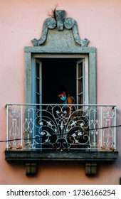 Cascais, Portugal - May 18, 2020: Woman wearing a protective face mask as seen through a historic balcony during the Coronavirus Covid19 outbreak