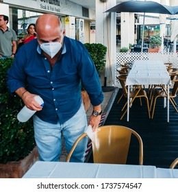 Cascais, Portugal - May 21, 2020: Man wearing a face mask cleans a restaurant table to reduce the spread of the Covid-19 virus