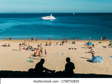 Cascais, Portugal - May 22, 2020: Sandy beach in Cascais near during the summer. This beach is known as Praia da Conceicao. Beachgoears practicing social distancing in times of Covid-19