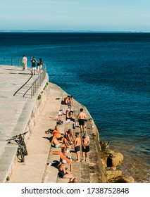 Cascais, Portugal - May 22, 2020: People relax next to the water in Cascais near Lisbon, Portugal during the summer