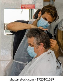 Cascais, Portugal - May 4 2020: Barber cuts a client's hair during the coronavirus outbreak. Both must wear protective facemask according to government rules to slow the spread of the virus