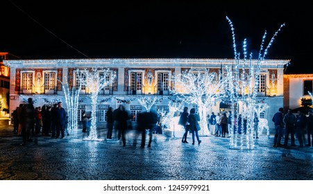Cascais, Portugal - Nov 30, 2018: Main Square of Cascais covered in bright illuminated Christmas lights and seasonal decorations at night. Long exposure of people, lively atmosphere