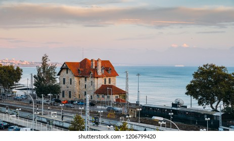 Cascais, Portugal - Oct 18, 2018: High perspective view of commuters at Cascais railway station at sunset, 30km west of Lisbon, Portugal. Cruise ship in background