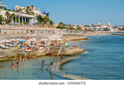 Cascais, Portugal - Sept 29, 2018: Families relax at the Oceanic Pool Alberto Romano in Cascais. Coastline of Estoril is visible in the background