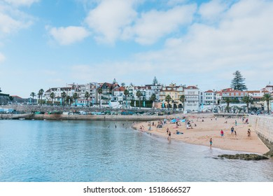 "CASCAIS, PORTUGAL - Summer 2019: Both tourists and locals enjoy the sun and calm water in the ""Praia da Ribeira"" in the town of Cascais."
