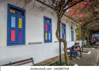 Casco Viejo, Panama City/Panama-March 3, 2018: Couple sitting on bench in beautiful tunnel with colorful windows behind them
