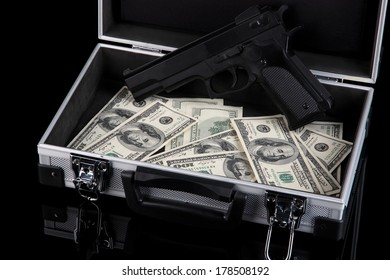 Case with money and gun, isolated on black