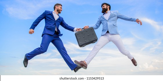 Case with raise your business. Successful transaction between businessmen. Briefcase handover in heaven blue sky background. Easy deal business. Businessmen jump fly mid air while hold briefcase.