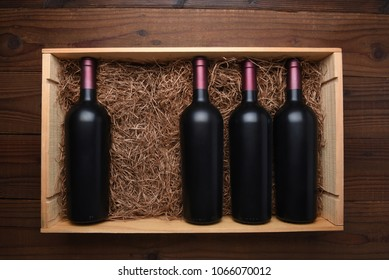 Case of Red Wine: Top view of a wood case of red wine bottles with one bottle missing, the case is filled with packing straw.