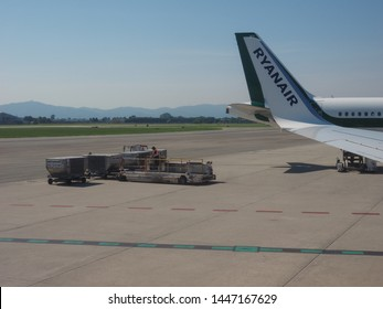 CASELLE, ITALY - CIRCA JUNE 2019: Aircraft ground cargo handling services at Sandro Pertini Turin airport by Aviapartner and Ryanair plane