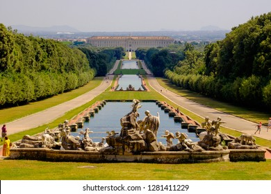 Caserta, Campania / Italy - 07 18 2018: The 'Reggia di Caserta', in the background, is a former royal palace and an example. The huge garden is 3 kilometers long and has sculptures and canals.
