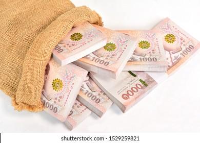 Cash 1000 baht banknote Thai in sack bag studio shot on white background.