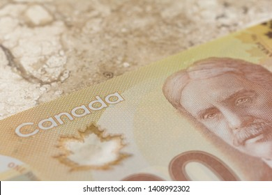 Cash bills from Canadian currency. Dollars. Closeup on marble table.