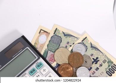 Cash and calculator on white background. Japanese money (yen)
