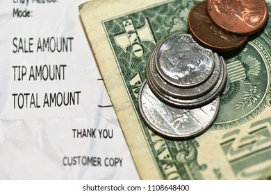 Cash change with classic receipt, coins and dollar bill close up.