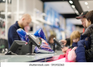 Cash desk with card payment terminal, computer screen and cashier serves customers in clothes store