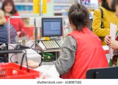 Cash desk with cashier serves customer in modern supermarket