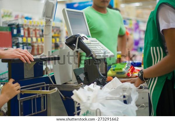 Cash desk with cashier serving customers in supermarket