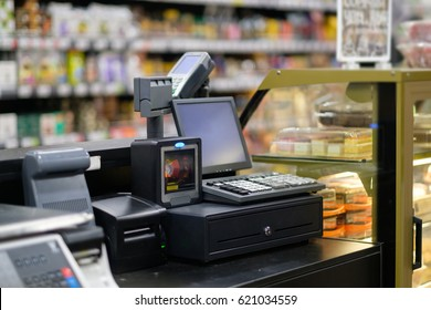 Cash desk with computer screen and card payment terminal in bakery department in store