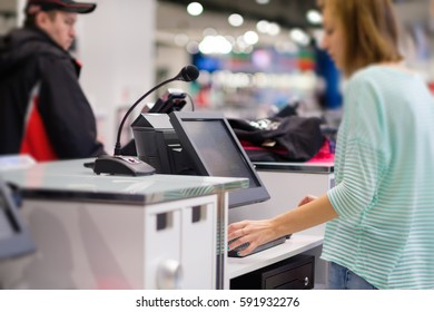 Cash desk with computer screen and cashier serves customers in clothes store