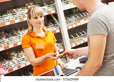 cash desk female worker accept payment card at hardware shop