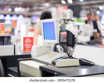 Cash desk terminal  with cashiers and customers on blurry background