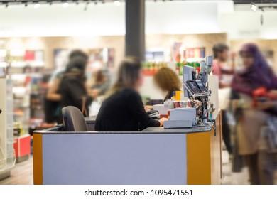 Cash desks with cashier serves customers on blurry background