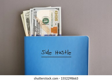 Cash dollar money in a blue notebook with text written on cover SIDE HUSTLE, on grey background, concept of making more money from side job with writing or freelance job