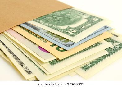 Cash dollars in paper envelope close-up.