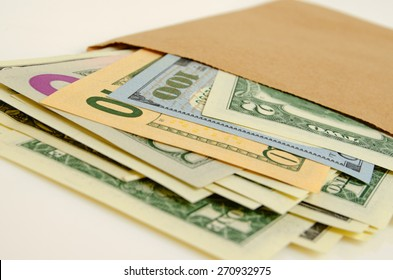Cash dollars in paper envelope close-up.