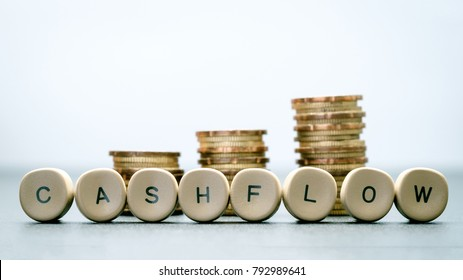CASH FLOW letter block and stack coins, business concept.