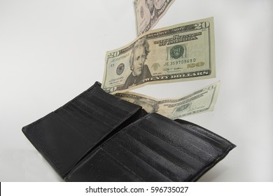 Cash flying out of billfold/Spending Money/Currency is flowing out of a wallet
