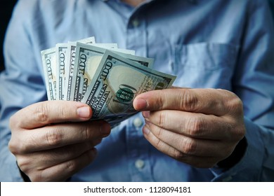 Cash in hands. Profits, savings. Stack of dollars. Man counting money. Dollars in man's hands. A man in business clothes with dollars. Success, motivation, financial flows, wealth. Stack of dollars.