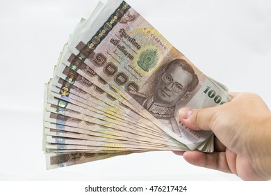Cash in Hand.Thai money - Baht.Pile of various currencies isolated on white background.Thai baht banknote coin isolated on white background.Many of Thai Baht background.Thai currency.