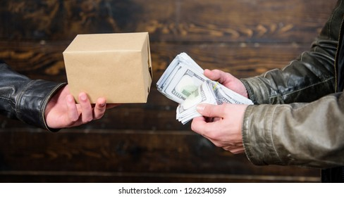 Cash money and box with forbidden goods exchange. Illegal deal concept. Money cash in hand of criminal man. Crime and illegal profit. Break law. Dealer and buyer of illegal item. Buy illegal products.