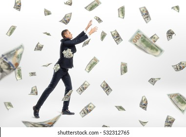 A lot of cash money flying and a businessman catching them on the white background. Success aspiration. Prosperous business. Earning a lot og money.