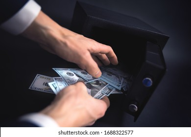 Cash Money Safe Deposit. Symbol of money safety. The man withdraw dollars from small Residential Vault. Toned soft focus picture.
