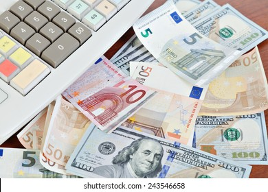 Cash register and different paper currencies foreground