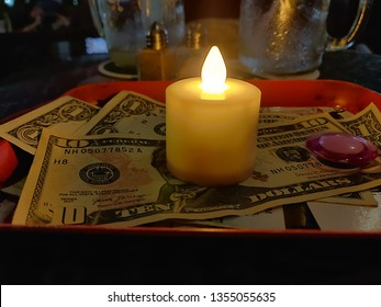 Cash Tip on restaurant and bar table with an LED candle for a waiter who provded great service and the kitchen team who cooked a great meal. USD 11 in Gratuity.