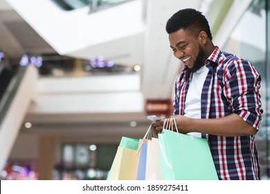 Cashback Bonus. Happy African Man Holding Shopping Bags And Smartphone In Mall, Using Discount App, Looking At Phone Screen And Smiling, Enjoying Online Offers, Standing In Modern Department Store