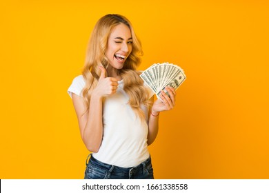Cashback. Excited woman holding money banknotes and showing thumb up over yellow background