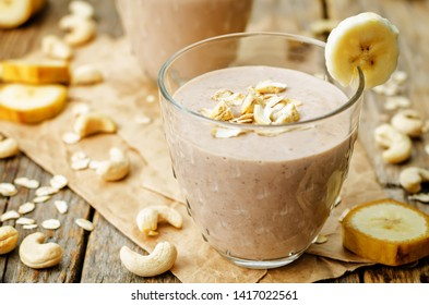 cashew banana cocoa oats smoothie on a wood background. the toning.selective focus