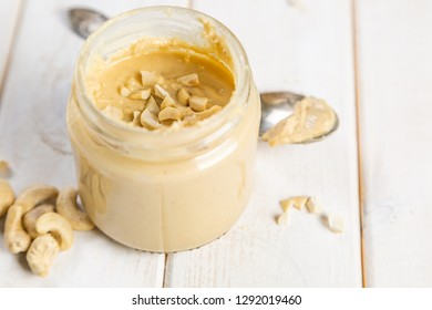 Cashew butter in glass jar, white wood background