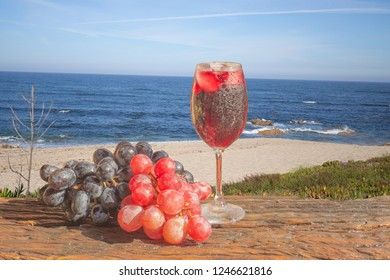 Cashew drink to refresh in the summer. Glass with ice, over wooden balcony decorated for carnival, with beach scenery in the background