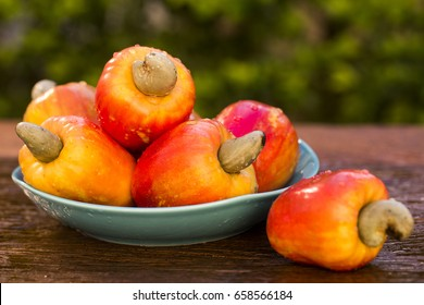 cashew fruit over a wooden surface.