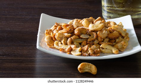 Cashew nut mix with salt in white dish and whisky in glass, All put on  brown wooden table / Still Life image and select focus with space for texts