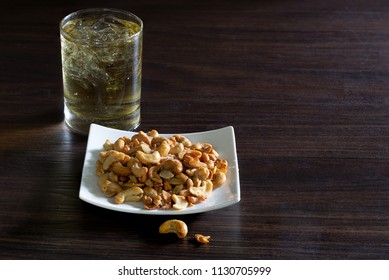 Cashew nut mix with salt in white dish and whisky in glass, All put on  brown wooden table / Still Life image and select focus and with space for texts
