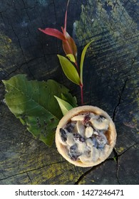 Cashew nut pudding, peanuts and raisins on green and yellow leaves (Ceylon Oak's leaves, the leaves of the Christina tree) are all placed on old stumps.