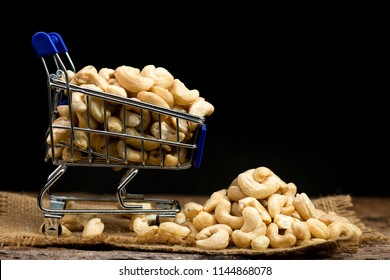 Cashew nuts in miniature shopping cart on dark background.